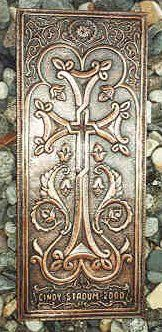 """A beautiful Armenian cross, made of copper.  """"This cross was commissioned to commemorate Cindy Stadum. You will notice """"wings,"""" flowers, and a sun symbol. Many of these cross images have wing-like designs to denote holiness or """"flying,"""" sacred words that fly to the heavens or fly to us from Heaven.  You will see the wings on the bottom of the cross."""""""