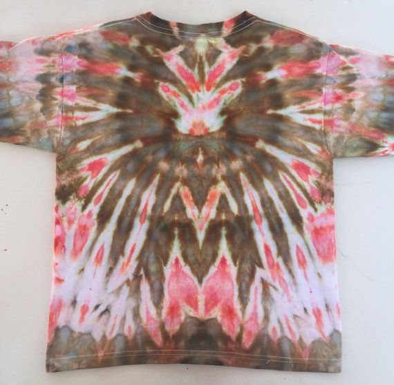 This is a vibrant hand-dyed t-shirt for kids reminiscent of a tribal feather necklace! Use your imagination to find interesting images in the design. This one of a kind ice dyed item is unique and a great gift for one of the young ones in your life! Colour- Brown, Salmon, White Size- Medium Youth (10-12) Brand- M&O Youth  To create this artistic design ice is used to deposit professional quality dye onto the fabric and the abstract art is created over a period of 24 hours. This item has…