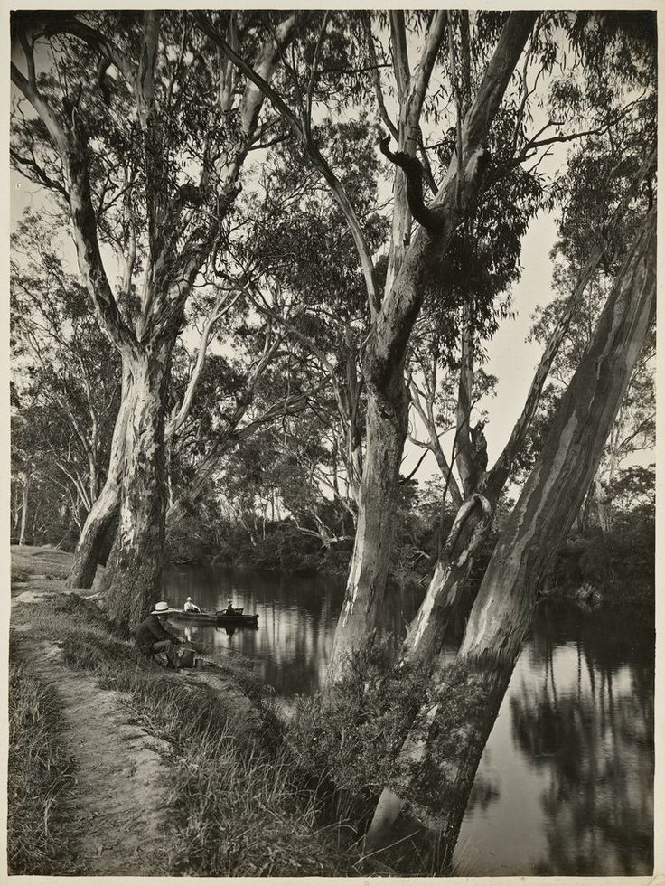 View shows a river with trees on either bank, a man fishing on the left with men in a small boat behind him. Circa 1910-1930.