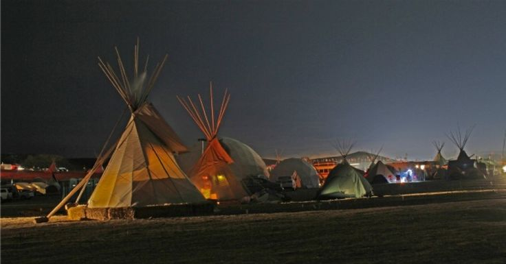 """Earth-force meets money-force at Standing Rock. I'm so relieved I'm here. It scares me to think that I might have missed this.We get up at dawn. Four hundred people walk slowly in a light snow to the river by the camp. A teacher is talking. His headdress is a crisscrossing of long, narrow feathers. He is of the Havasupai, the people who live by the blue-green waterfalls at the bottom of the Grand Canyon. He calls out across the river. """"Water is life! Take me! My heart beats with you!"""""""