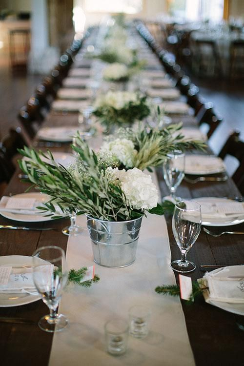 Silver pail centerpieces with hydrangeas and olive leaf | Brides.com