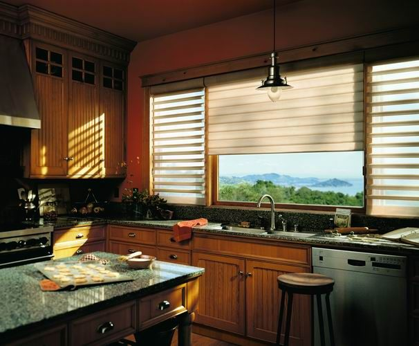 Soft diffused light through this LUXAFLEX® Pirouette® Shading brightens this dark wood & stone kitchen. #kitchen #blind #pirouette