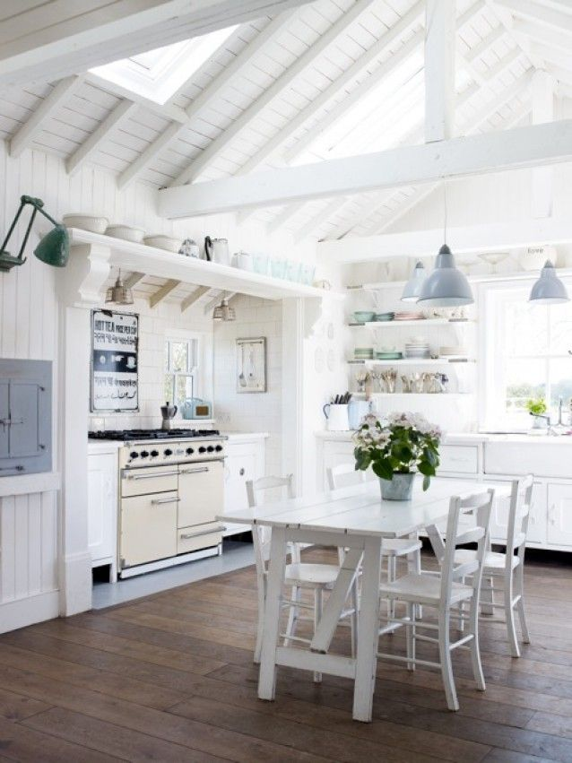 Like the rich wood floor and the all white with a touch of color with the lights and dishes.