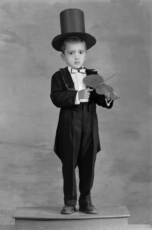 Dandy violinista. En este retrato de un niño elegante y vestido como Dandy con su sombrero, su smoking y corbata de moño, lo que impresiona no es su atavío; también porta un violín de utilería. ¿A parte de galán era músico?  Foto: RUTILO PATIÑO, Jaral del Progreso, Guanajuato, México, ca. 1935. Fondo Rutilo Patiño / Colecciones Fotográficas de Fundación Televisa