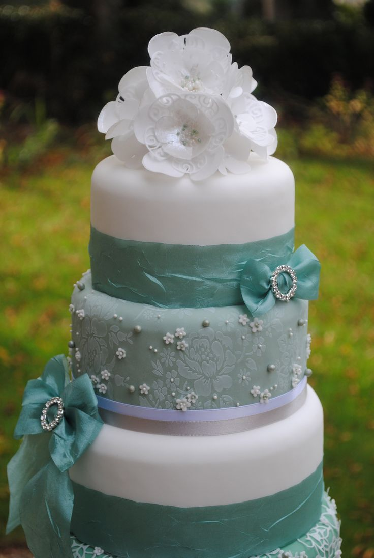 Wafer paper flowers are a quick and easy way to add stunning details to the top of your tiered cakes. The flowers have been coloured using metallic paint and extra details added to the centre using edible pearls. www.cakecrafting.co.uk.