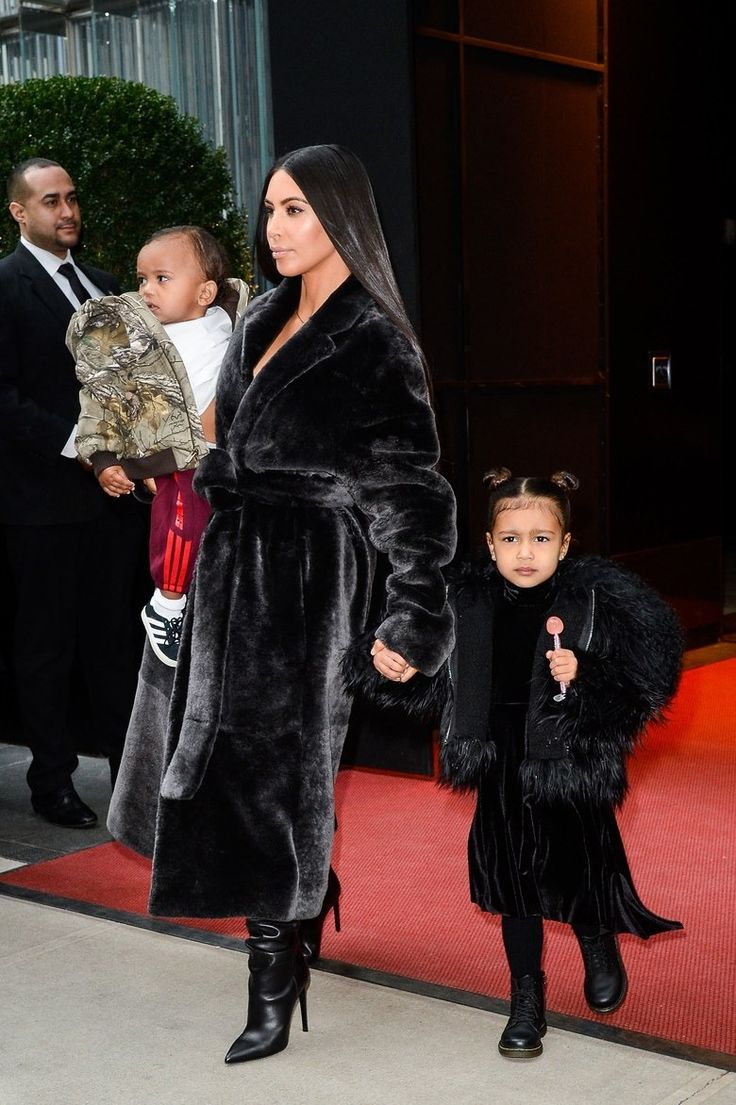Kim Kardashian West, North West, and Saint West in coordinated statement coats in New York City.