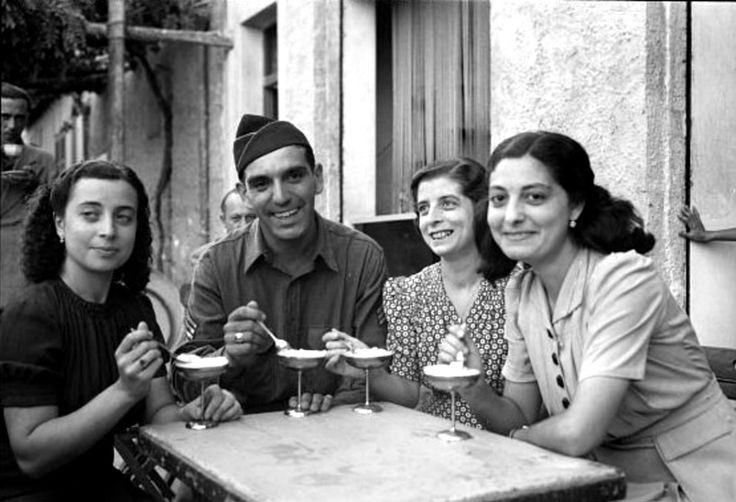 U.S. Army Sergeant Vincent J. Crivello has ice cream at a sidewalk café in Palermo while getting acquainted with three of his Italian relatives he discovered following the successful Allied invasion of Sicily, Operation Husky (September 1943). Photographed by Nick Parrino