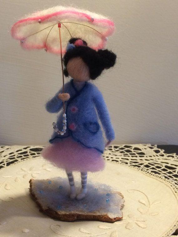 Het meisje onder een paraplu. De hele compositie is gemaakt in de techniek van droog vilten. Ik blijf bij twee kleuren: licht blauw (de kleur van het water) en roze. De basis is van de korst van eucalyptus en bedekt met een dun laagje van lichte blauwe wol met dezelfde kleur kralen die lijkt op waterdruppels.  Hoogte van de pop is 14 cm.