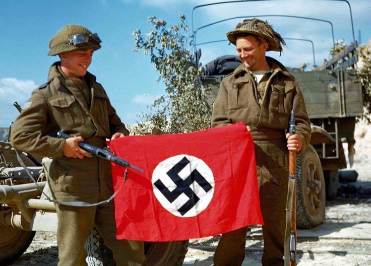 Two Canadian soldiers raise a Nazi flag which they captured in a quarry south of Hautmesnil, France, August 1944.