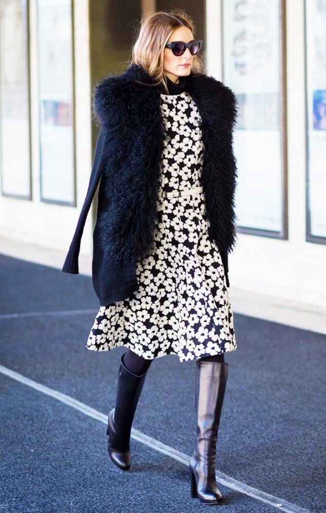 Olivia Palermo wears a floral dress, fur cardigan, cat-eye sunglasses, tights, and knee-high leather bots