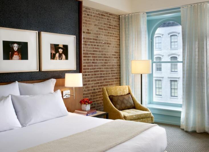 Deborah Berke // 21c Louisville Museum Hotel Bedroom Suite // brick wall, felt bed headboard, yellow chair and blue painted wall hidden behind white curtains