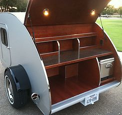 Juno Custom Teardrops a 5x10 Teardrop Trailer. This custom teardrop features custom woodwork throughout the cabin, where there are custom selves, and a teardrop galley with a custom slide-out cooler.