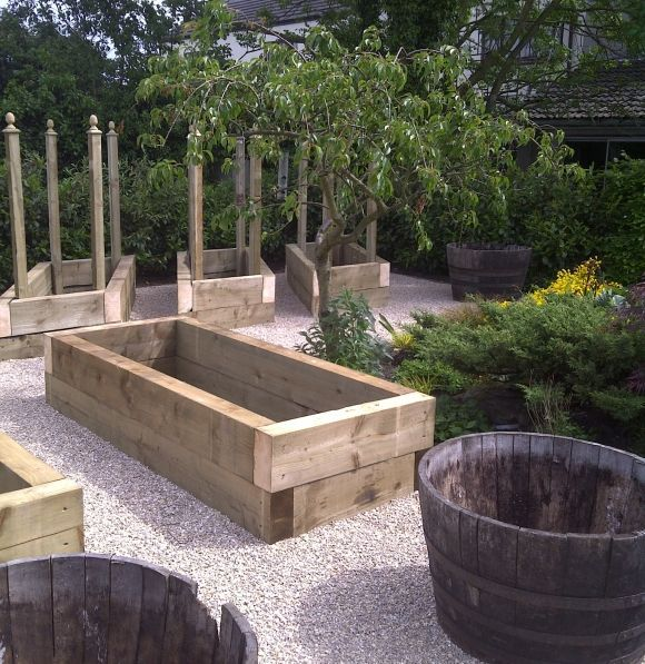 Sleeper Raised Beds with wine barrels in between for herbs, and trees. Maybe the granadilla on an arch! LOVE all these ideas.