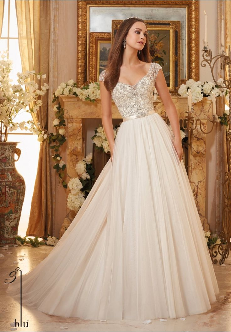 Wedding Gowns By Blu featuring Crystallized Embroidery on Soft Tulle Ball Gown Removable Beaded Satin Belt included. Colors Available: White/Silver, Ivory/Silver, Ivory/Champagne/Silver