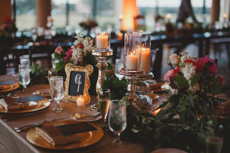 guest tables at the reception were dressed with garland, pillar candles on mercury glass pedestals and flower arrangements of pink roses and ranunculus in vintage brass.