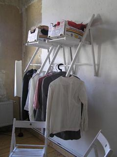 DIY Closet out of folding chairs.  I love how brilliantly simple this idea of creating your own closet space with folding wooden chairs is.