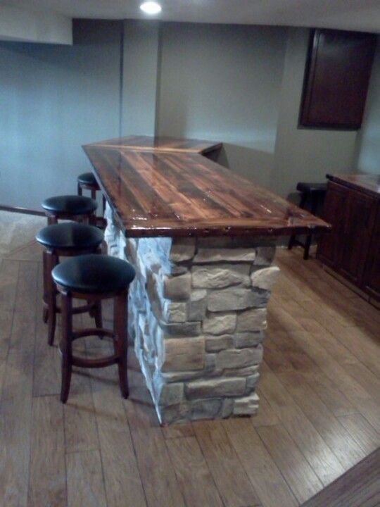 Basement bar penninsula rocked with reclaimed barn wood countertops sealed with epoxy gel coat. Without rock would look better.