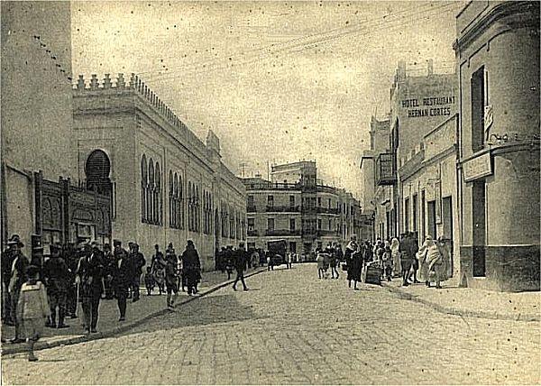 """Calle Alfonso XIII: aquí arrancaba la calle principal de Tetuán. A la derecha, la farmacia Rodríguez (luego Pérez) y, enfrente, el edifico del Mercado, que luego fue derribado y ahora ocupa el edificio que fue de La Unión y el Fénix. Al fondo, la casa de Benatar, donde estuvo originariamente la fotografía """"España"""" y después el fotógrafo Morales."""