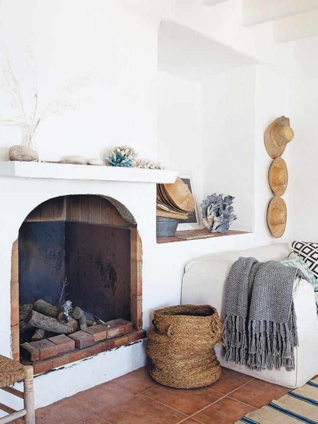 A Spanish beachside home with white walls, fireplace, tile floors, and natural textiles