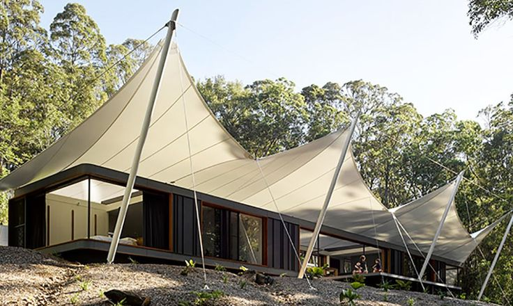 A tent house in a rainforest clearing in Australia easily transitions from indoor to outdoor space.