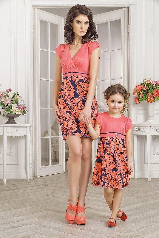 Комплект летних платьев для мамы и дочки, розового цвета. Платье для мамы облегающего кроя, с завышенной талией, длиной выше колена. Вырез изделия глубокий, V-образный, с запахом. Рукав в виде двойного крылышка. Верх платья однотонный, без рисунков и узоров, нежно-розового, кораллового цвета. Юбка в