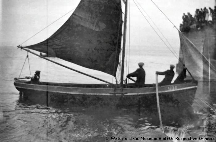 """Three men in a fishing boat at Helvick Pier, Ring, Co. Waterford"", Ireland c.1930. The photo was taken after a regatta"