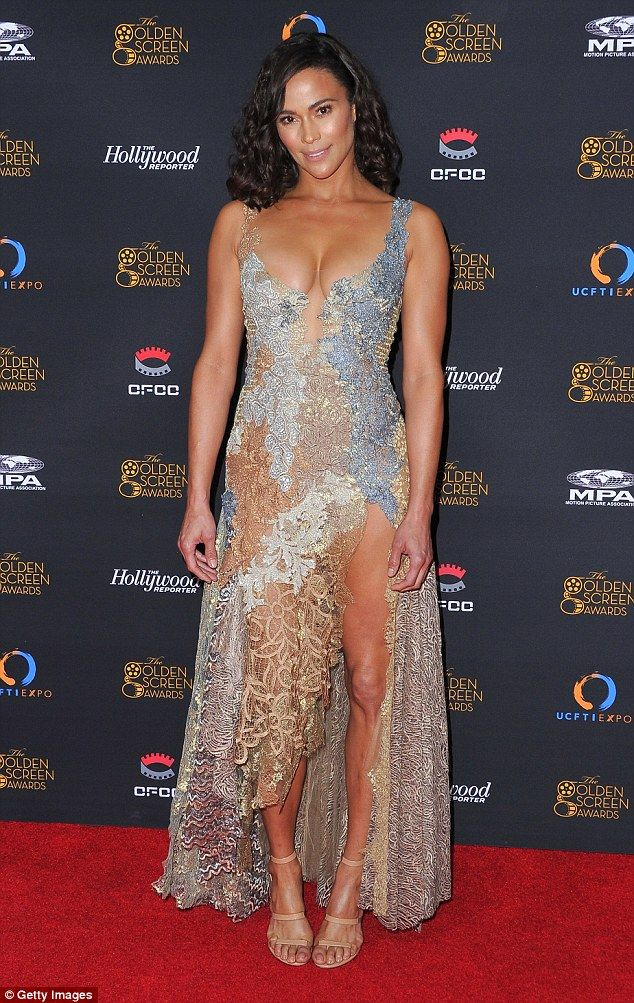 Flesh-baring: The multi-colored diaphanous gown was slit to the hip at the front revealing her enviably toned and tanned legs with her feet showcased in nude strappy heels