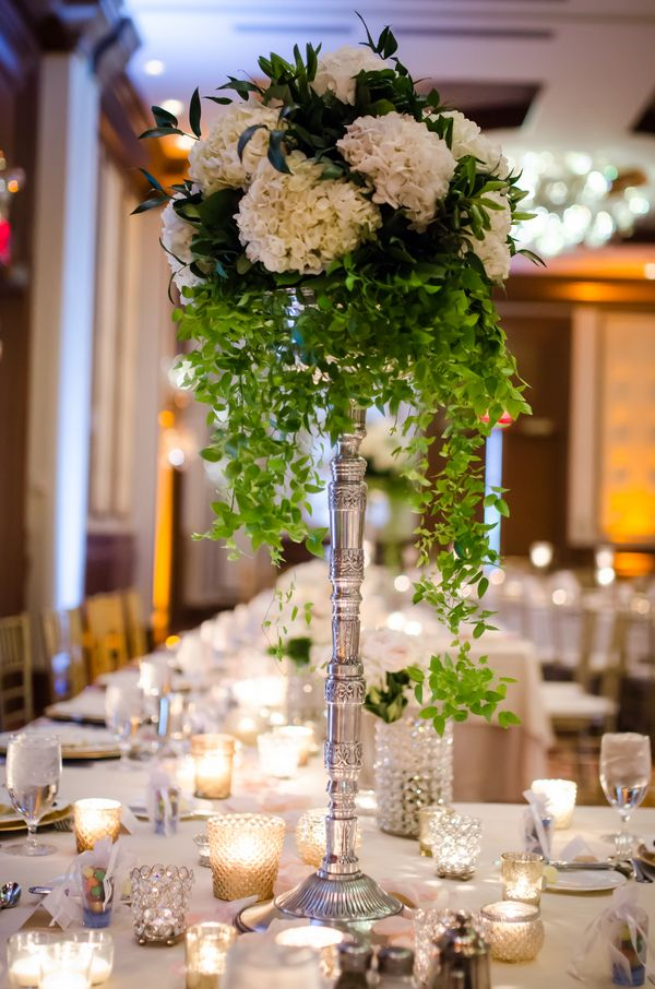 Beautiful tall wedding centerpiece with white hydrangea and cascading greenery (Heather Marie Photography)