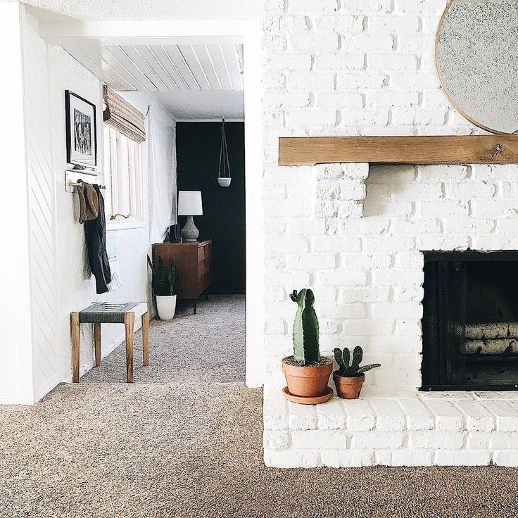 Restoring home, brick fireplace, white brick, wood mantle, terra cotta, cactus, southwest, southwestern decor, boho, bohemian, birch logs, round mirror, simply white Benjamin Moore