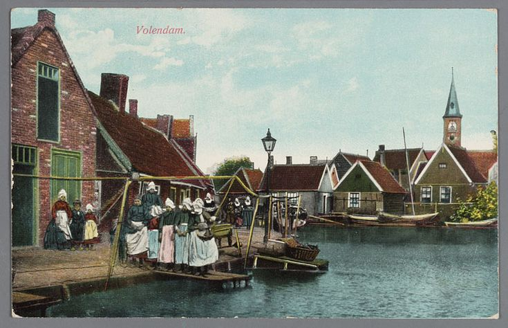 Een groep vrouwen en kinderen in dracht poseren links van een straatlantaarn bij het water aan de Meerzijde met het Breekje te Volendam. Rechts de huizen van het Doolhof met de R.K. kerk. 1905-1914 #NoordHolland #Volendam