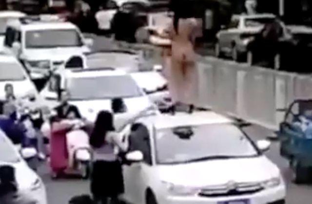 Câmeras de segurança flagraram uma mulher que perdeu a linha, as roupas e resolveu dançar nua em cima de um carro aleatório. O fato inusitado aconteceu na hora do rush.
