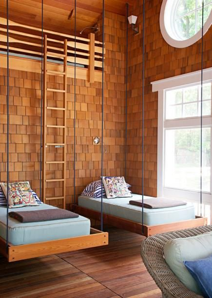In the shingle-sided screen porch of this Michigan home, new wooden oars form a railing around a loft hideaway.  Cute!