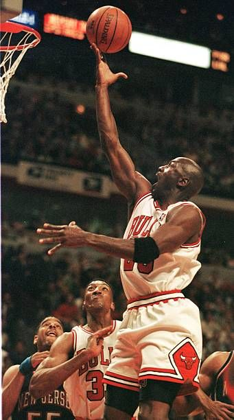Michael Jordan of the Chicago Bulls drives to the basket past teammate Scottie Pippen and Jayson Williams of the New Jersey Nets 24 April during the...