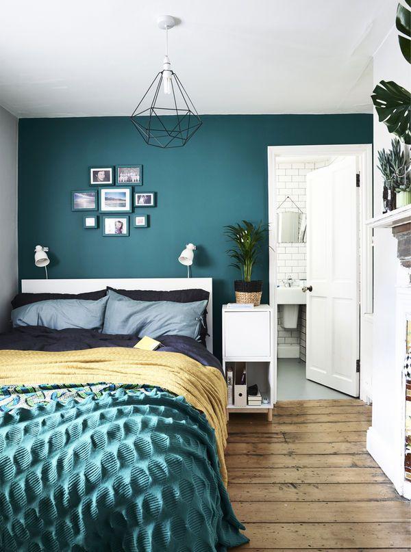 Soverom med grønn vegg og fargerikt sengetøy.