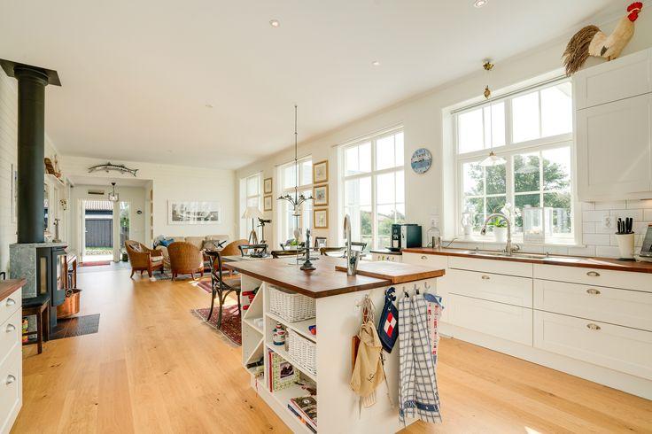 Öppen planlösning mellan kök och vardagsrum, med stora fönsterpartier längs hela väggen mot havet!