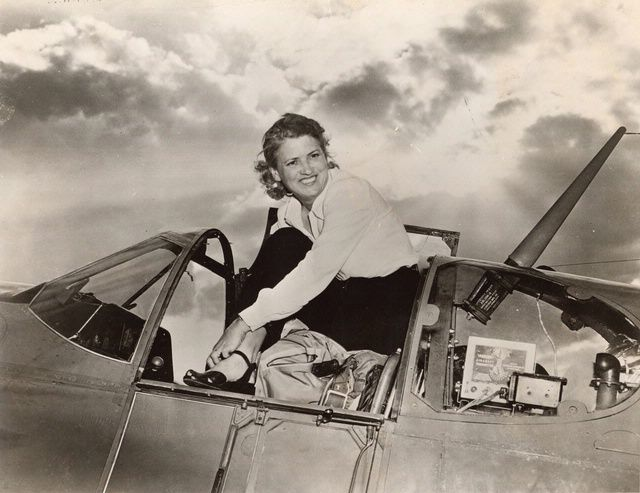 """Jacqueline """"Jackie"""" Cochran, June 2, 1947. Cochran's career spanned four decades from the 1930s to the 1960s. Among her many accomplishments, she won the prestigious long-distance Bendix Trophy Race in 1937, founded the WASP (Women Airforce Service Pilots) during WWII, and became the first woman to break the sound barrier in 1953. Here she stands in the cockpit of her North American P-51B Mustang. SI-86-533"""