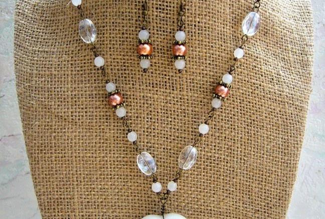 Veľké kamenné srdce s elegantným brúsením po celej ploche. Doplnené je perlami v marhuľovom odtieni, sklenenými mliečnymi guličkami a čírymi oválkami s jemným pokovom a kovovými guličkami. Set obsahuje aj náušničky z rovnakého materiálu.  Všetko na starozlatých komponentoch.