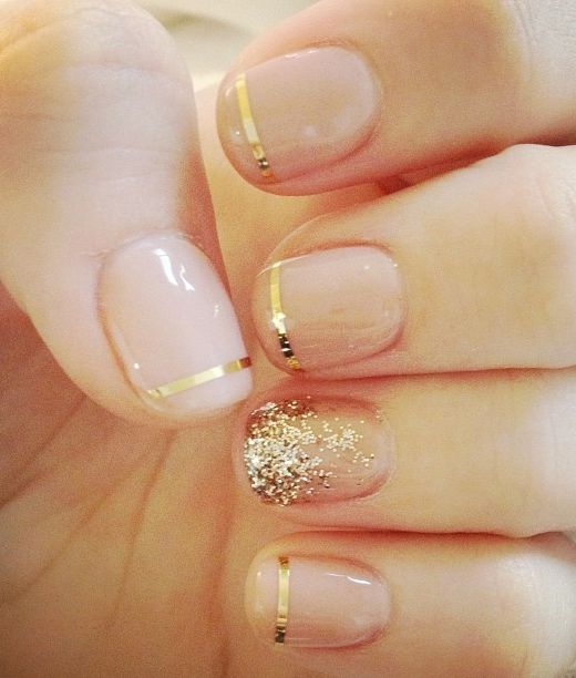 Nude nails with gold tips and an accent nail. /