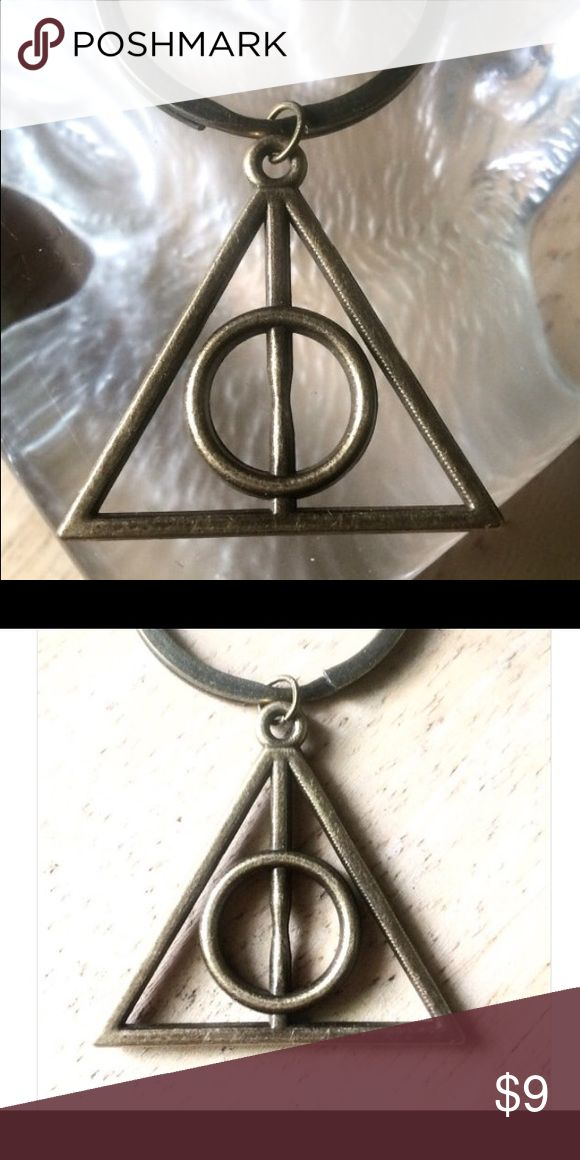 """Triangle Keychain Pendant or Bag charm Light weight key ring with a bronze triangle pendant. Can be used as a key chain, a bag charm or a zipper pull.  In Harry Potter this is the """"Deathly Hallows"""" symbol representing three objects:  -The wand (vertical line) -The Resurrection Stone (circle)  -The Cloak of invisibility (triangle)  Alternate meanings are: -The absolute (highest spirit) within the self, the infinite power of the self -Holy Trinity Accessories Key & Card Holders"""