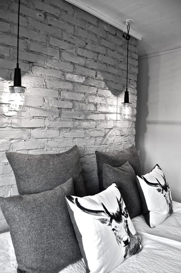 White and grey bedroom. Industrial lighting. Bare brick walls. Textured scatter cushions.