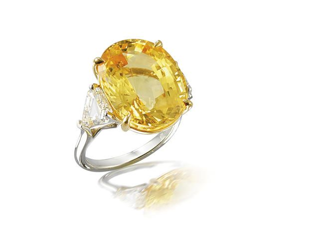 A yellow sapphire and diamond ring The oval mixed-cut yellow sapphire, flanked by triangular-cut diamonds, mounted in platinum and 18k gold, yellow sapphire approximately 20.55 carats, diamonds approximately 2.55 carats total.
