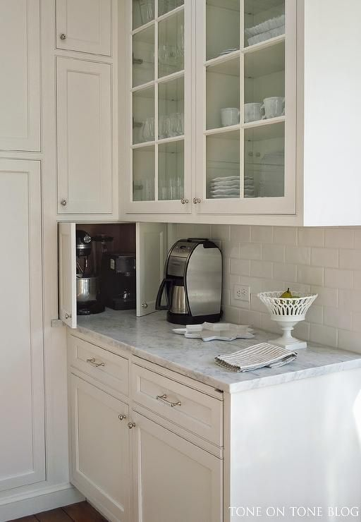 White kitchen features glass-front upper cabinets and white lower cabinets paired with carrera marble countertops and a white glazed subway tile backsplash.