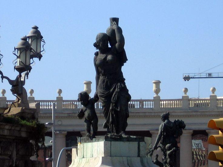 Saúde Pública. 1928-1929. Bronze e mármore. Miquel Oslé (1879-1960,  Barcelona, Espanha) e Llucià Oslé (1880-1951, Barcelona, Espanha). Na Fonte Comemorativa da Exposição de 1929, na Praça da Espanha em Barcelona, Catalunha, Espanha. Pedestal com figura feminina coroada por ervas, carregando um jarro, um ganso e uma criança com uma concha na mão. É a deusa Hygeia (a Salus romana),  que monitora a saúde dos humanos. O ganso é um símbolo de vigilância, e a concha, a água.  Fotografia: Canaan.