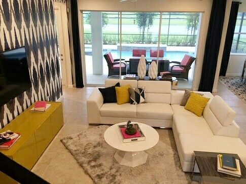 Living room, great room, inground pool, lanai, outdoor furniture, couches, accent wall, modern interior design,  floor rug, white and yellow, resort homes, vacation homes, holiday villas, Kissimmee, Florida, Orlando, Veranda Palms, Park Square Homes