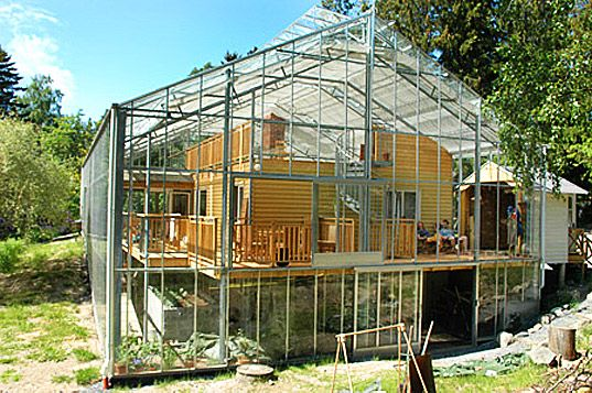 Having a greenhouse attached to my house is something I want, but never thought about enclosing my home in the greenhouse.