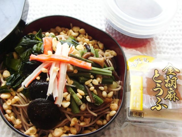 A cold soba bento. Soba noodles with lots of toppings (vegetables, wakame seaweed, crabstick, and tenkasu - tempura batter bits; sauce on the side, and a storebought goma dofu (sesame tofu).