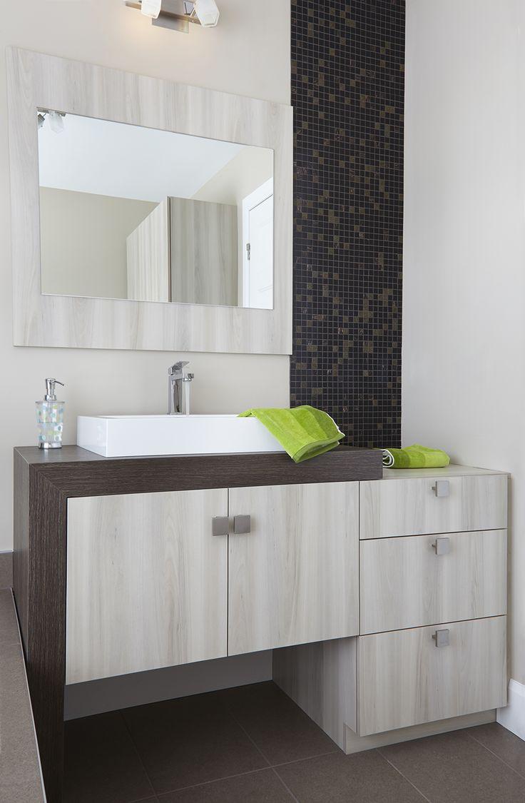 De couleurs contrastantes, cette vanité de salle de bains de style moderne marie un mobilier en mélamine de couleur poire de la côte à un comptoir en stratifié plus épais en forme de « L », de couleur sorbier d'automne. Le miroir est apposé sur un panneau en mélamine de la même couleur que la vanité, créant ainsi une continuité de ton.