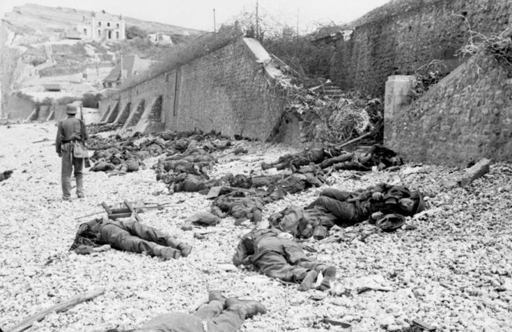 "The deadly result of enfilade fire during the Dieppe Raid of 1942: dead Canadian soldiers lie where they fell on ""Blue Beach"". Trapped between the beach and fortified sea wall, they made easy targets for MG 34 machineguns in a German bunker. The bunker firing slit is visible in the distance, just above the German soldier's head.France, Dieppe August 1942"