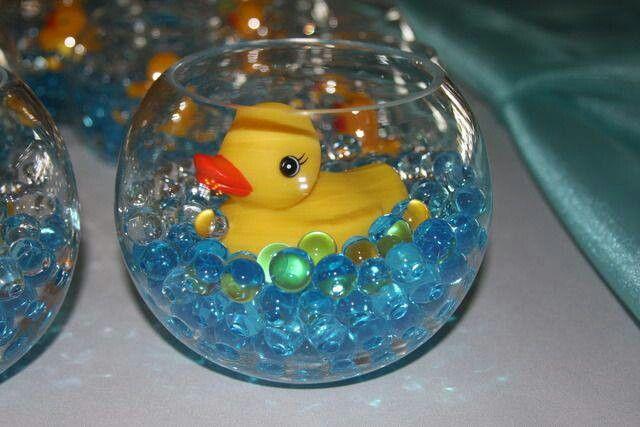 Cute baby shower centerpiece.  Nodig: Kleine ronde vaasjes, Badeendjes, Blauwe gel parels, glas kralen enz. Werkwijze: Vul de vaasjes voor +- de helft met de blauwe kralen. Zet de badeend middenin, en klaar is je centerpiece voor je babyshower.