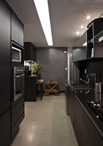 A iluminação geral da cozinha foi resolvida com longo rasgo no forro de gesso, onde foram embutidas lâmpadas fluorescentes; a bancada é de granito preto absoluto fornecido pela Mont Blanc. A cuba de inox é da Mekal e, a torneira, da Deca